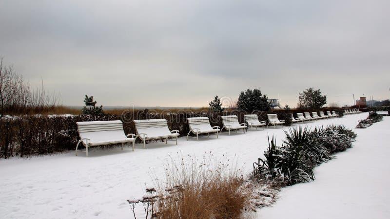 Banco e jardim pequeno no inverno imagem de stock royalty free