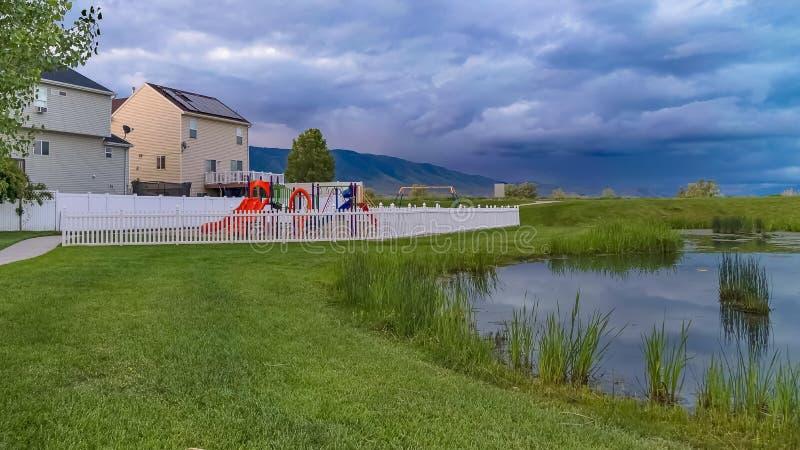 Banco e lagoa do quadro do panorama em um parque gramíneo com campo de jogos e casas no fundo imagens de stock royalty free