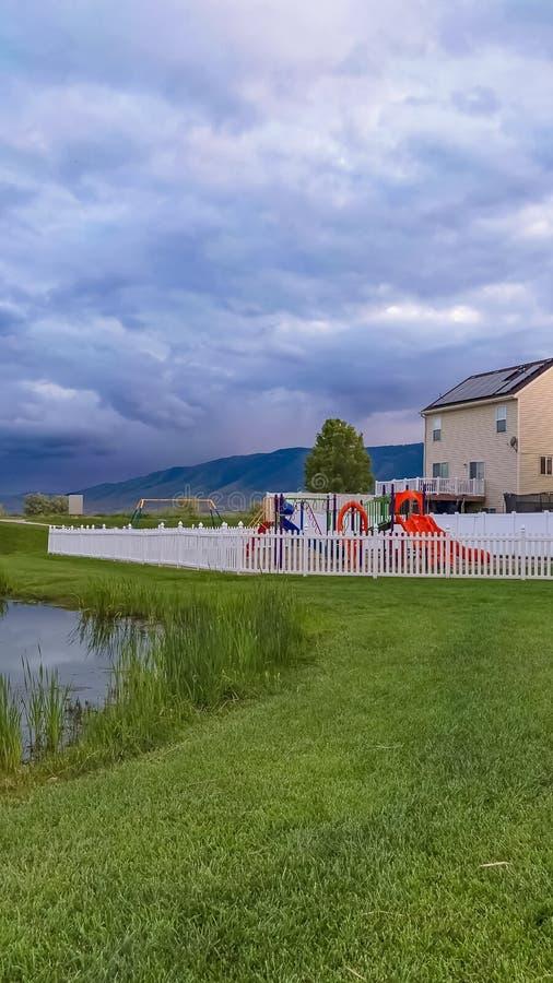 Banco e lagoa verticais do quadro em um parque gramíneo com campo de jogos e casas no fundo fotos de stock royalty free