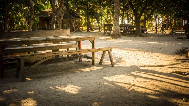 Banco e tabela de madeira na praia da areia com paraíso tropical da árvore na luz ensolarada imagem de stock
