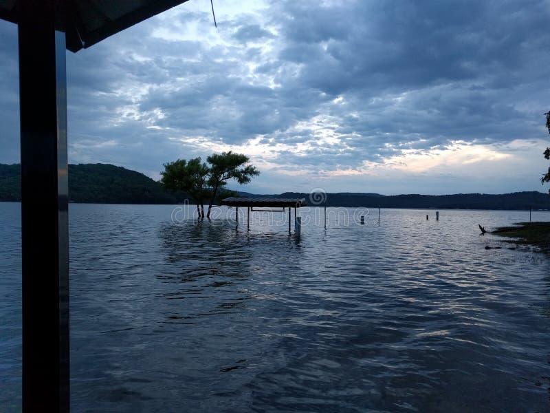 Banco ed albero sommersi in un lago su una sera nuvolosa immagine stock