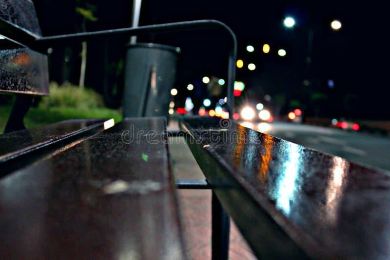 Banco en calle y las luces de la noche imagen de archivo