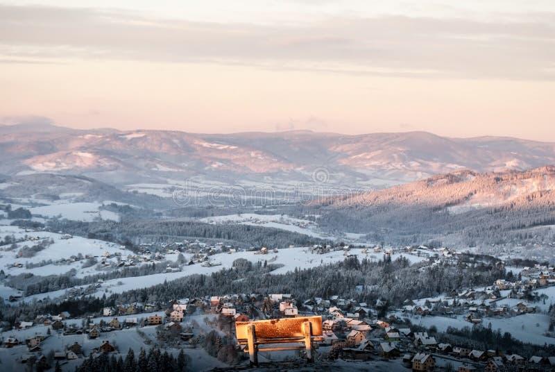 Banco en cumbre de la colina de Ochodzita con bramido y colinas del pueblo de Koniakow en el fondo en las montañas de Beskid Slas foto de archivo