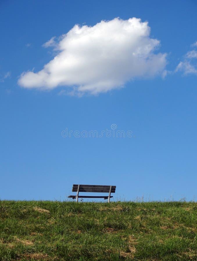 Banco en una colina con la sola nube blanca sobre ella fotos de archivo