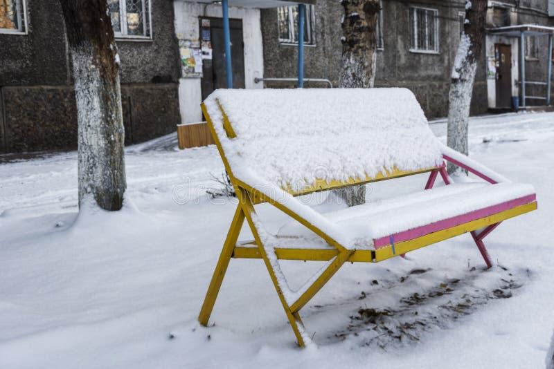 Banco en yarda nevada de la ciudad del invierno imagen de archivo libre de regalías