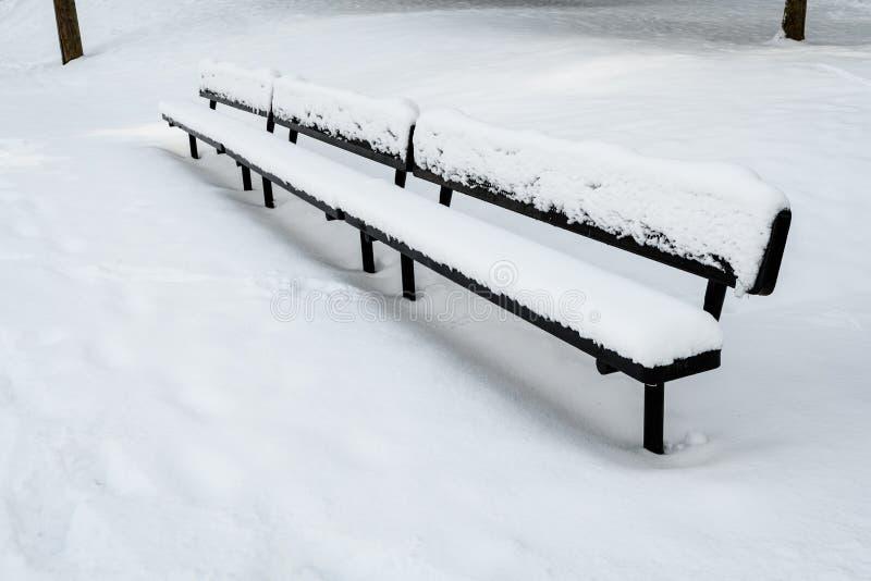 Banco espectador dos esportes pretos longos do metal coberto na neve em um campo nevado fotografia de stock
