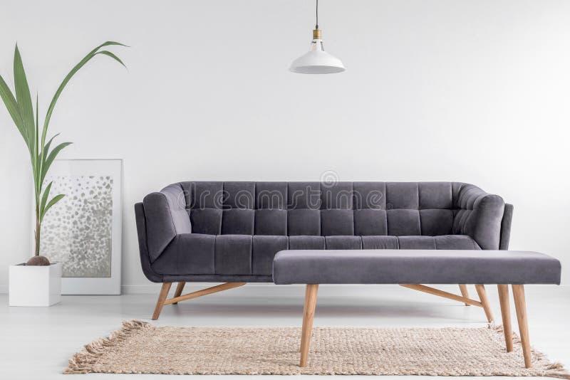 Banco estofado confortável em um tapete bege e um grande, sofá de veludo em um interior brilhante, branco da sala de visitas com  foto de stock royalty free