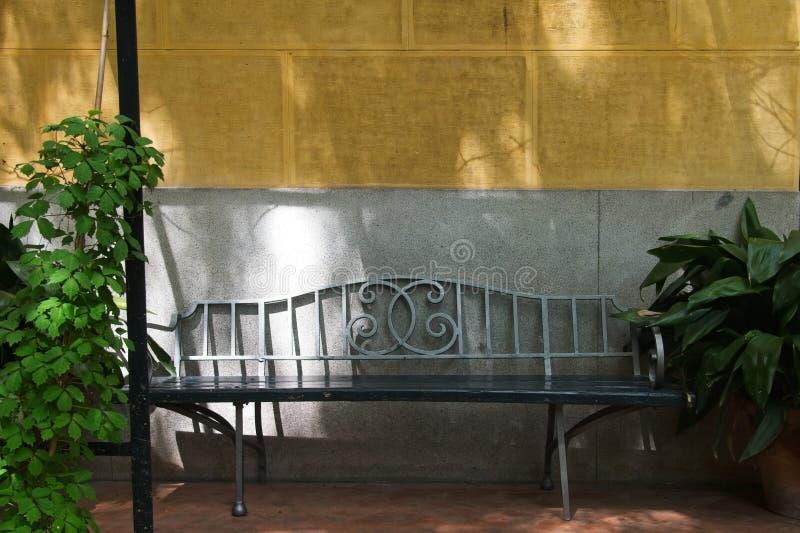 Banco exterior do ferro forjado bonito contra a cor mediterrânea do Bisque wal foto de stock