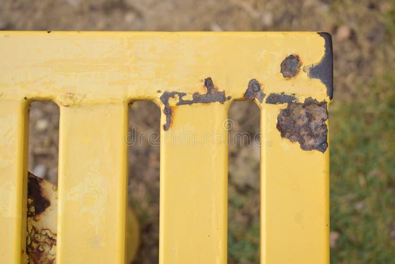 Banco giallo arrugginito in un parco fotografie stock
