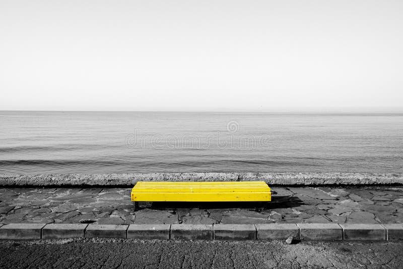 Banco giallo sul fondo in bianco e nero del mare fotografia stock libera da diritti