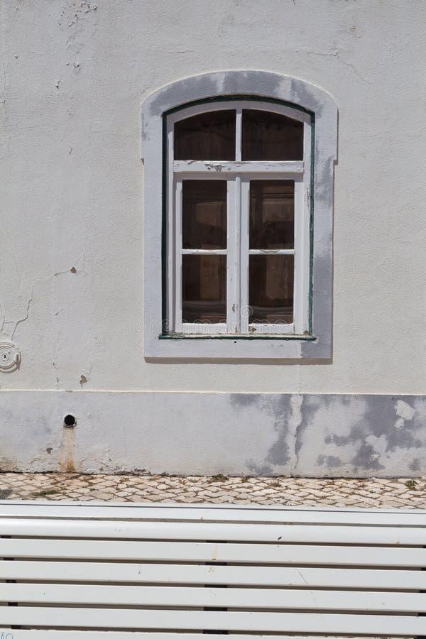 Banco, guijarros y pared blancos con una ventana imagenes de archivo
