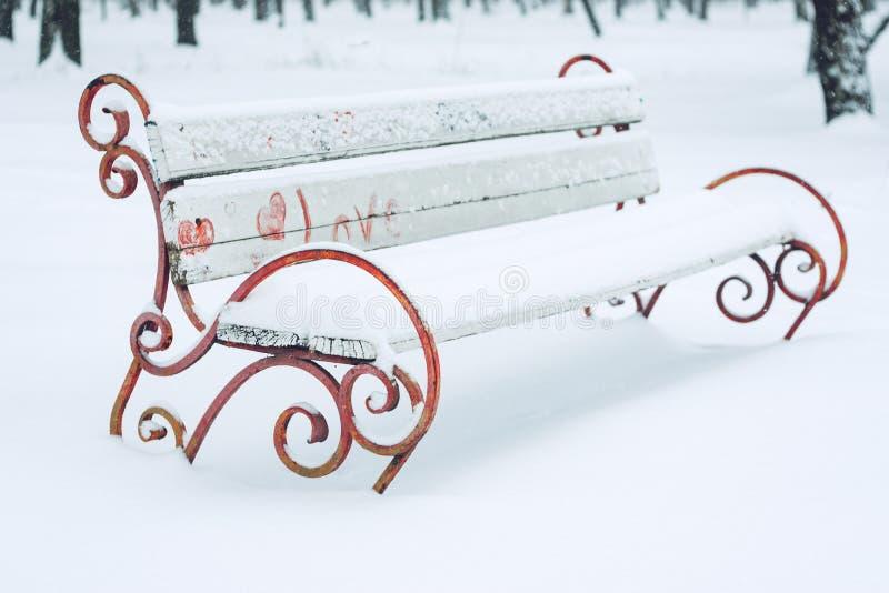 Banco innevato con cuore nel parco della città Metallo forgiato e banco ed alberi di parco di legno coperti da forte nevicata Inv immagini stock