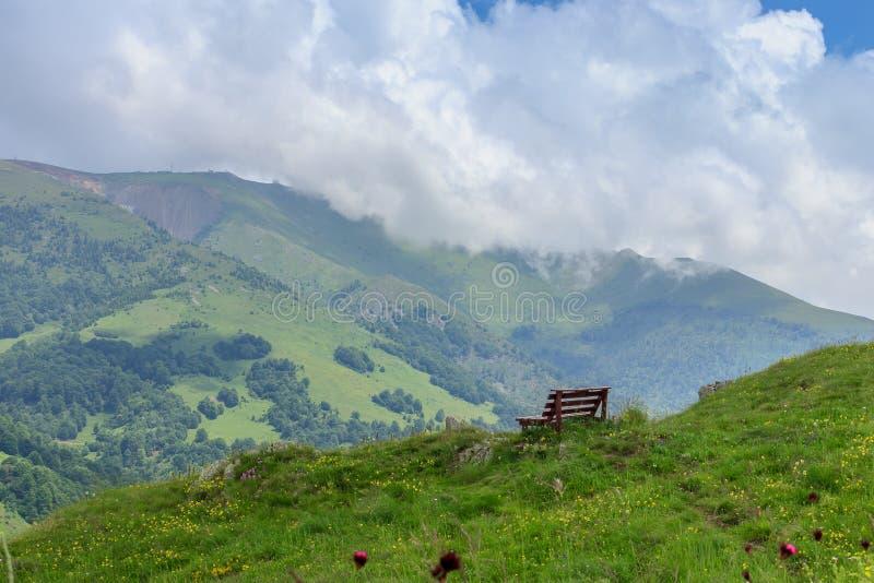 Banco na parte superior do monte e na vista bonita das montanhas arborizadas imagens de stock royalty free