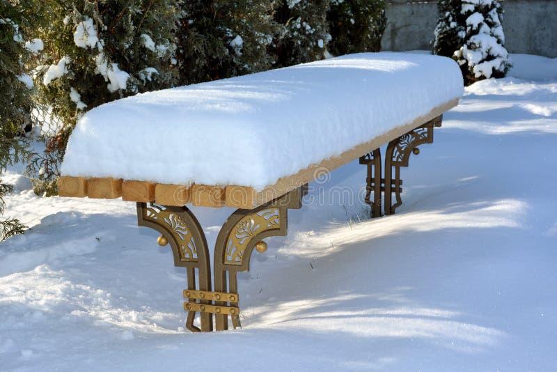 Banco no inverno coberto com as nevadas fortes fotos de stock