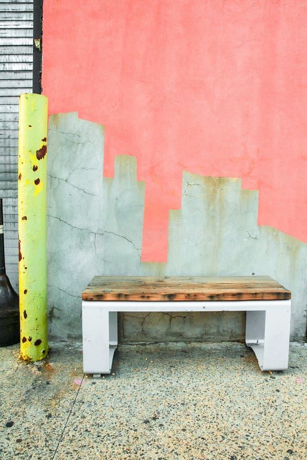 Banco no passeio contra a parede rachada coloridamente pintada do cimento fotos de stock