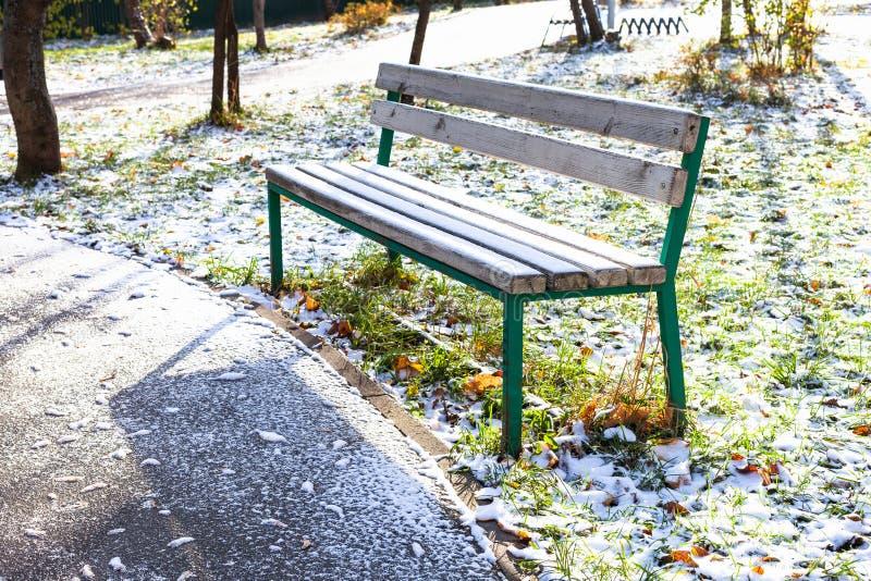 Banco perto do trajeto no jardim urbano coberto com a neve imagens de stock