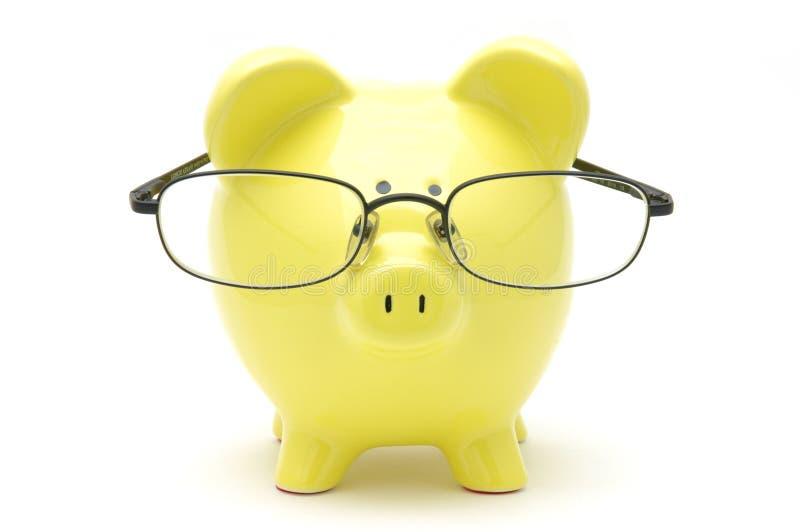Banco piggy amarelo com vidros fotografia de stock royalty free