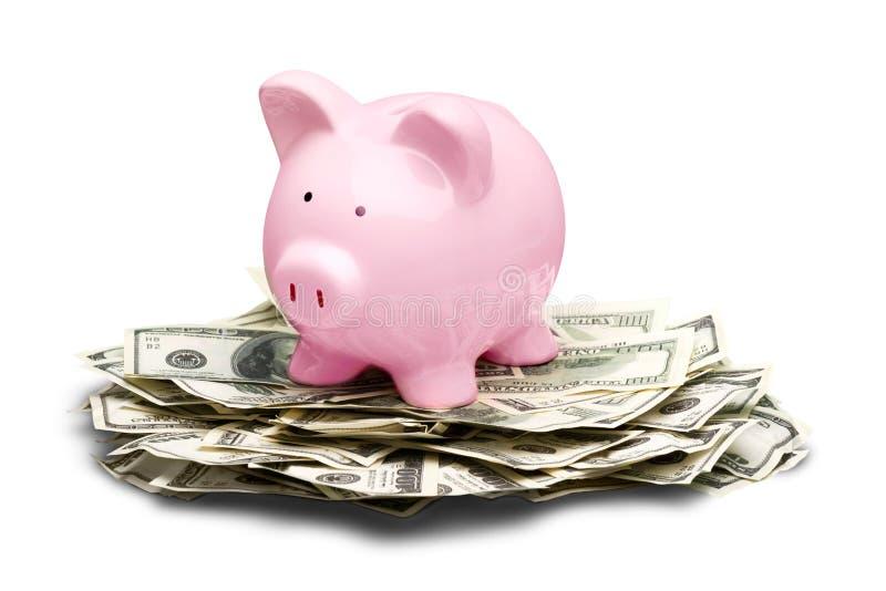 Banco piggy cor-de-rosa em contas de dólares no branco imagem de stock royalty free