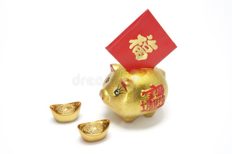 Banco Piggy dourado com pacote vermelho fotografia de stock royalty free
