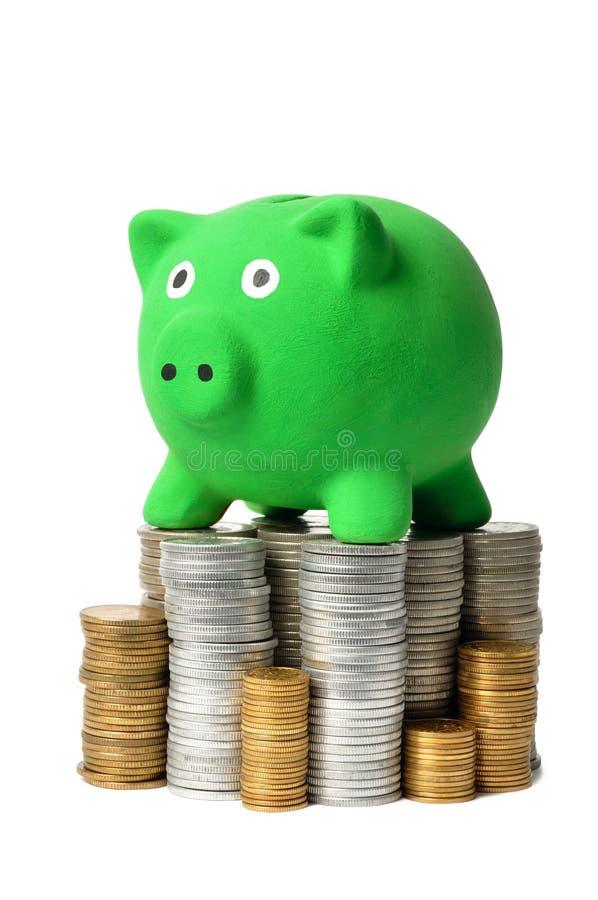 Banco Piggy e moedas verdes imagens de stock