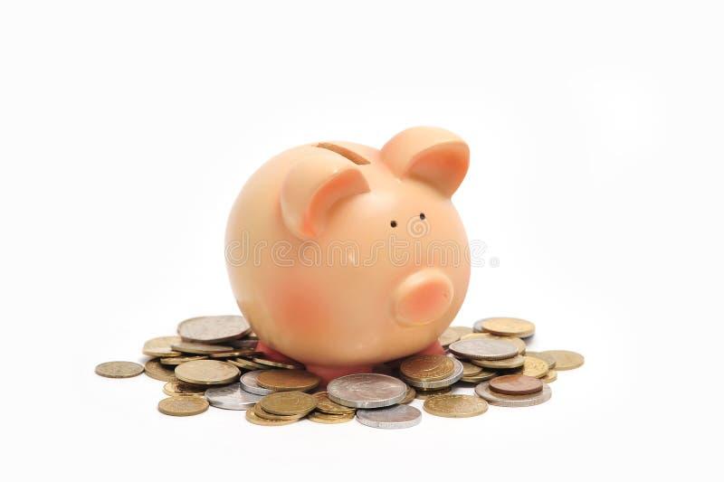 Banco Piggy que senta-se em moedas fotografia de stock