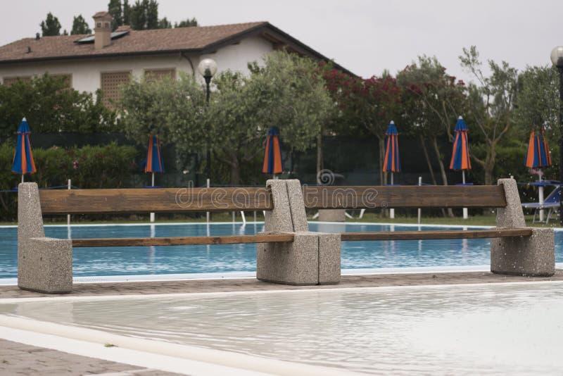 Banco por la piscina imagen de archivo