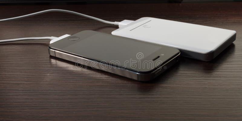 Banco portátil blanco del poder y teléfono móvil imagen de archivo