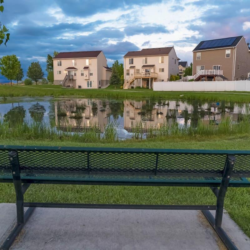 Banco quadrato del metallo di verde della struttura che affronta uno stagno brillante con la riflessione delle case e del cielo n fotografie stock libere da diritti