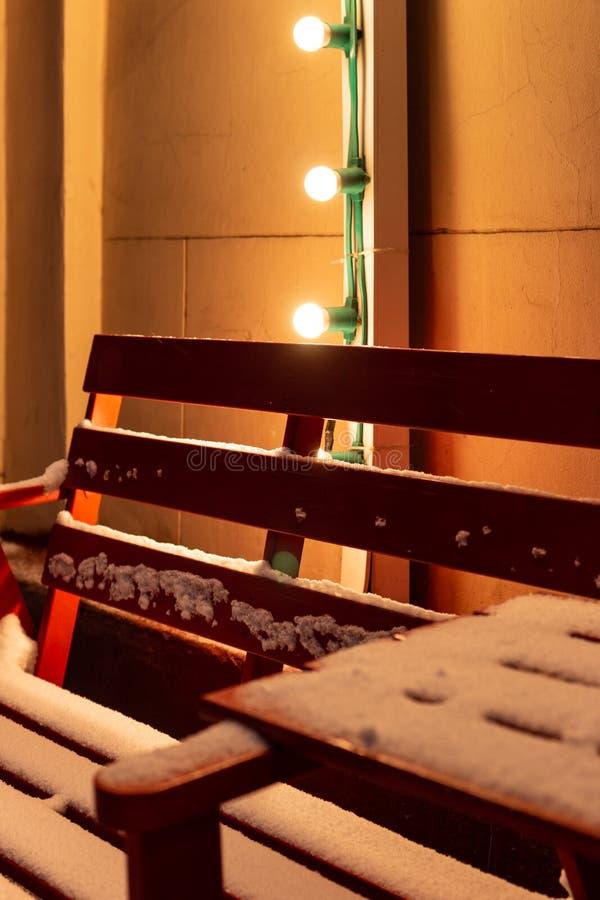 Banco rojo de madera y una tabla en el café al aire libre cubierto con nieve en el invierno foto de archivo libre de regalías