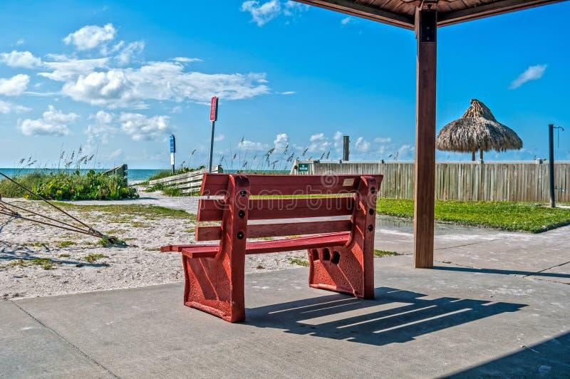 Banco rojo en la playa foto de archivo libre de regalías