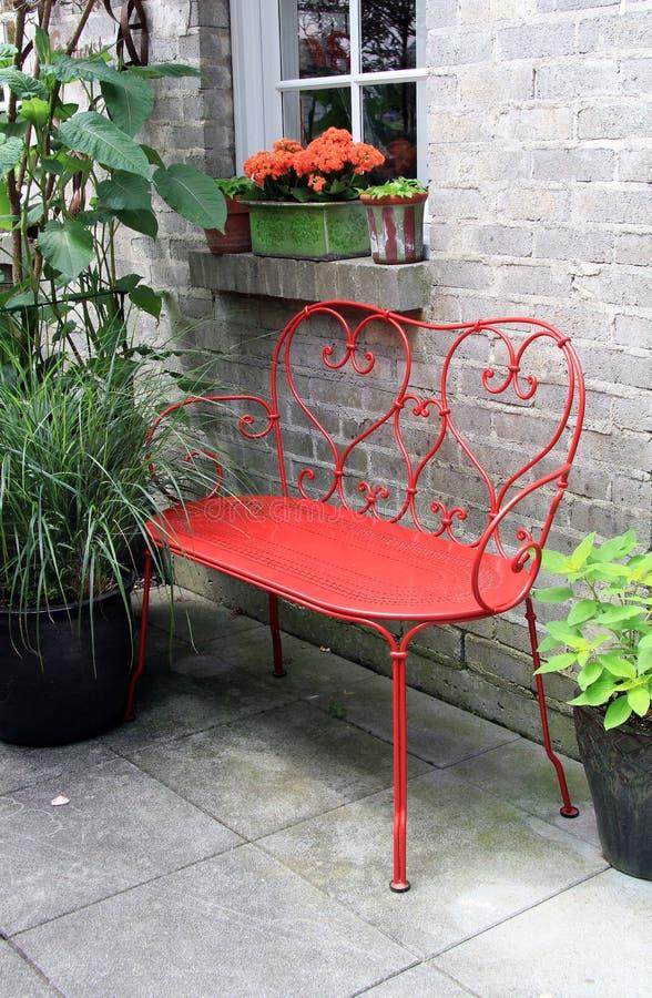 Banco rosso fuori su un patio immagini stock