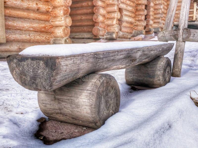 Banco ruvido di legno sotto la neve all'aperto sui precedenti di una casa dei ceppi fotografie stock