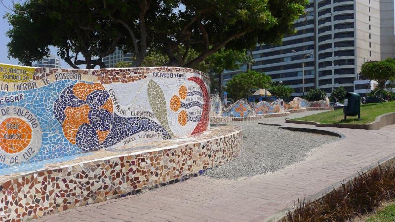 Banco tejado y edificios exteriores en un parque de Lima imagenes de archivo