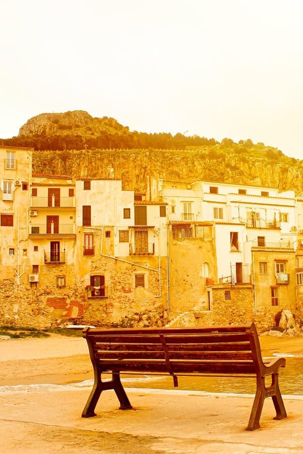 Banco vacío capturado en una imagen vertical en luz anaranjada brillante de la puesta del sol Tomado en la costa de la ciudad sic foto de archivo libre de regalías