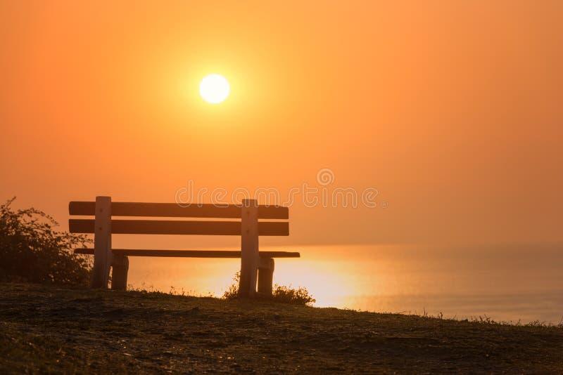 Banco vacío con la opinión del mar de la salida del sol que sorprende, la paz y el fondo romántico tranquilo del viaje imagen de archivo