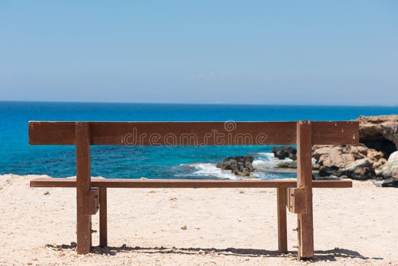 Banco vacío de madera con una opinión majestuosa del mar fotografía de archivo