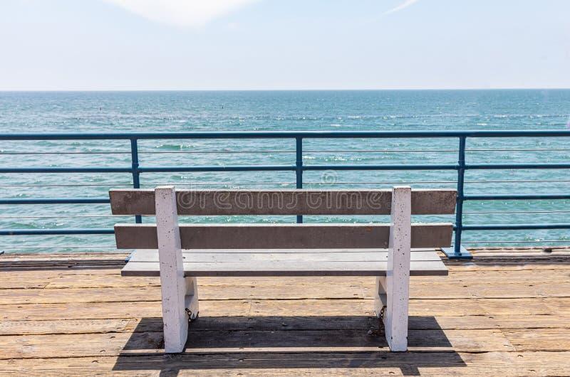 Banco vacío en cubierta de madera, el cielo azul y el fondo del mar foto de archivo