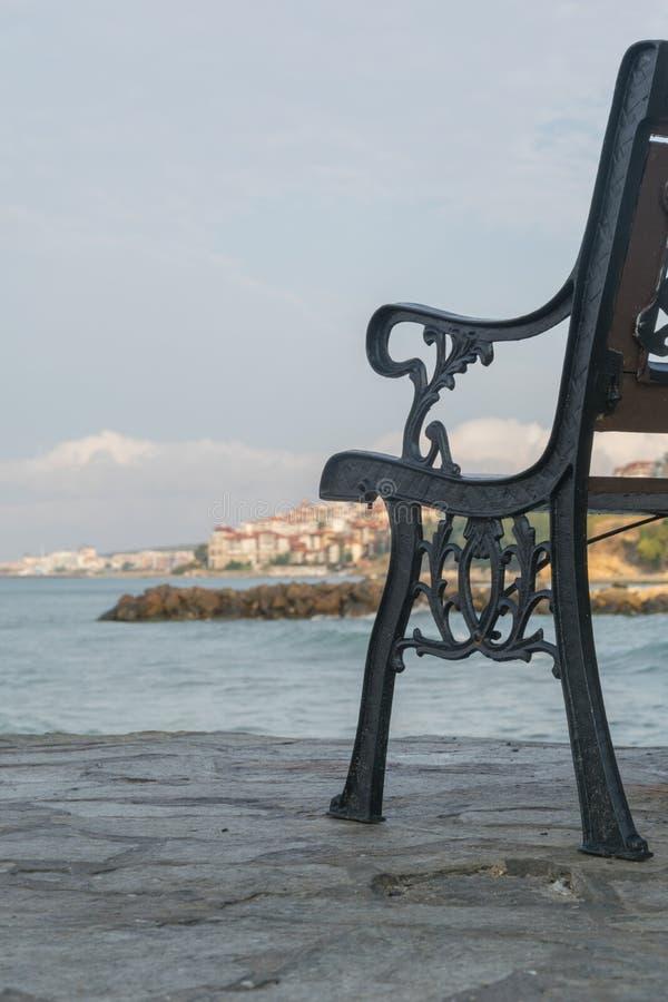 Banco vacío en el terraplén de piedra sobre el mar azul fotos de archivo