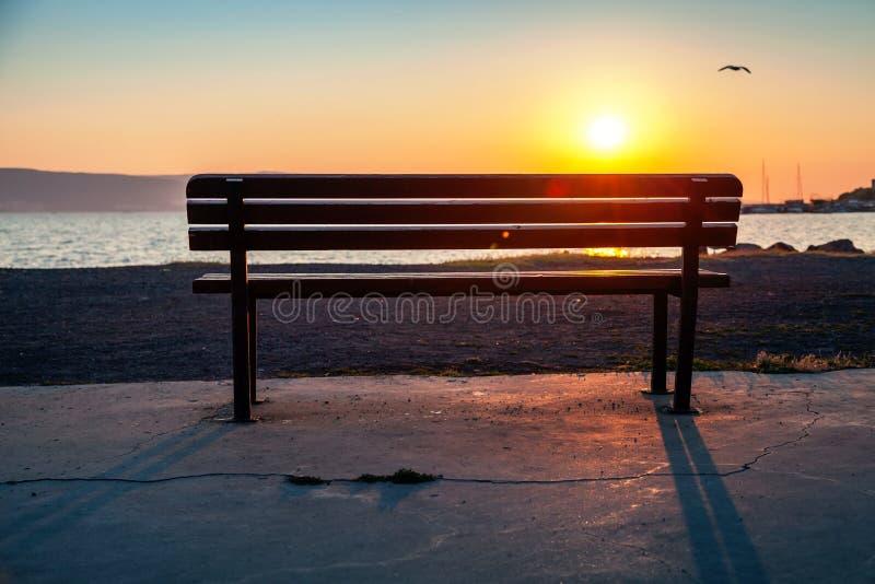 Banco vacío en una costa de mar con el sol brillante de la mañana fotografía de archivo libre de regalías