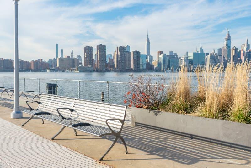 Banco Vazio com Plantas em um Parque em Greenpoint, Brooklyn Nova York, olhando em direção ao East River e à linha do horizonte d foto de stock
