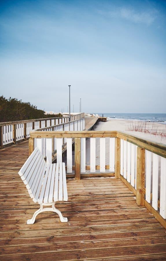 Banco vazio em um passeio à beira mar de madeira por uma praia foto de stock royalty free