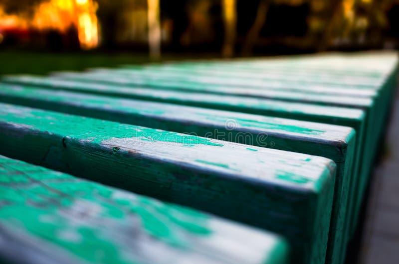 Banco verde del vintage de la aguamarina diagonal en fondo del parque imagen de archivo libre de regalías