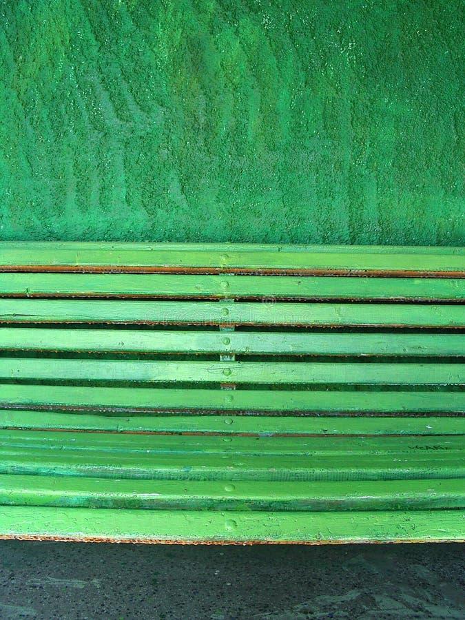 Banco verde em uma parede verde