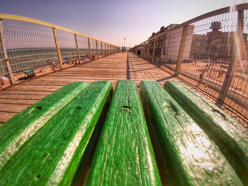 Banco verde en un embarcadero foto de archivo
