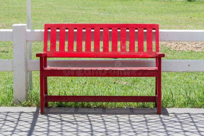 Banco vermelho no jardim fotos de stock royalty free