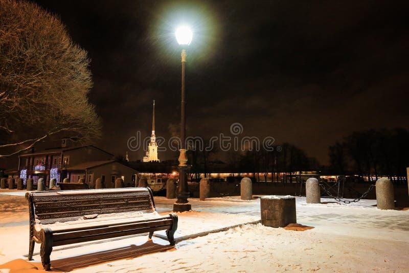 Banco, vicolo e iluminazione pubblica in precipitazioni nevose alla notte Paesaggio urbano di inverno in San Pietroburgo, Russia fotografia stock