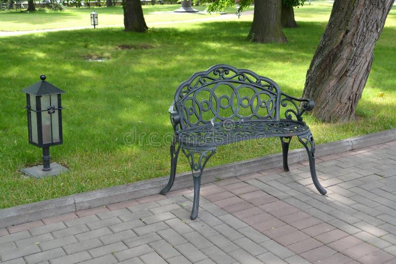 Banco y lámpara decorativos del metal en parque St Petersburg fotografía de archivo