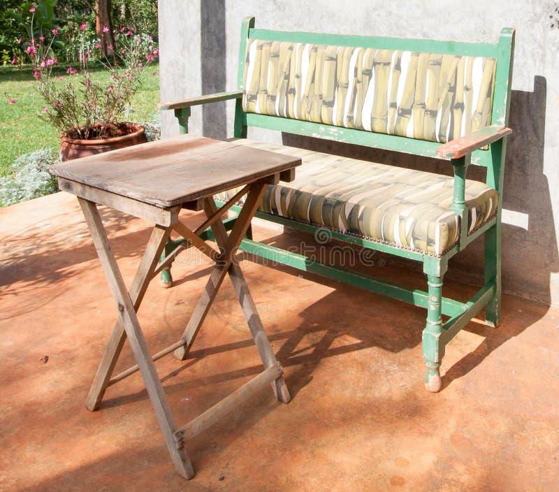 Banco y tabla soleados en patio del jardín fotos de archivo libres de regalías