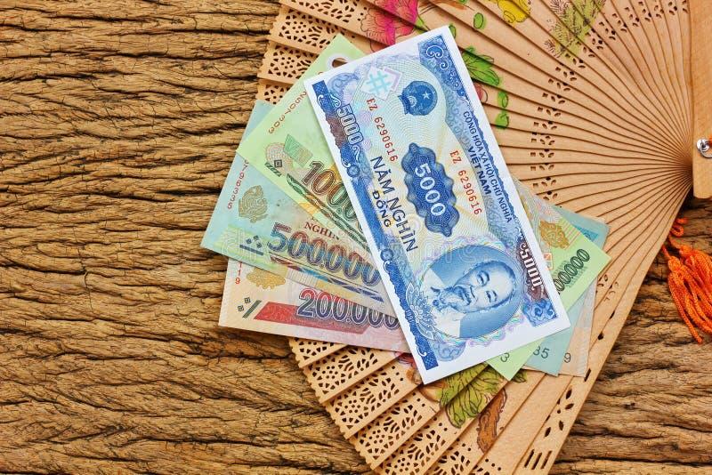Banconota dei fondi di Dong, Vietnam con il fan di legno cinese d'annata immagini stock libere da diritti