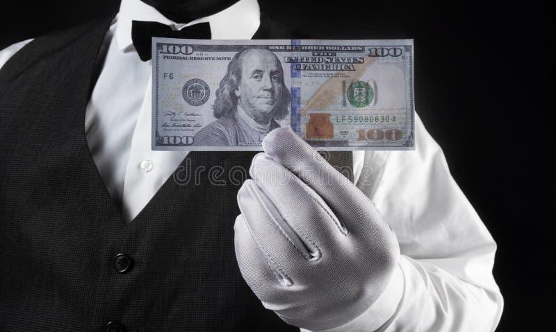 Banconota del dollaro della tenuta del cameriere in guanto bianco fotografia stock libera da diritti
